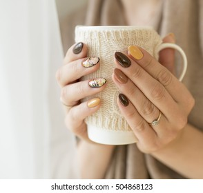 hands of autumn nails holding a cup of hot tea