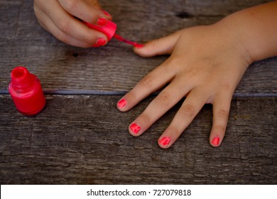Hands of a baby girl putting on her own nail polish