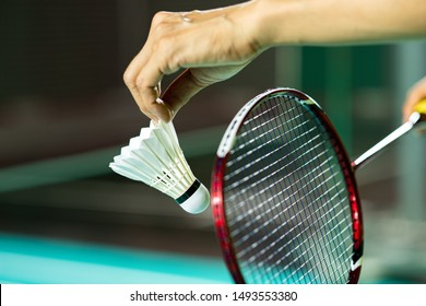 Hands of BADMINTON player holding racket and serving shuttlecock with blur Badminton court background, popular indoor sport concept