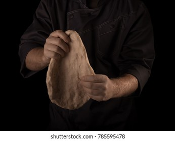 Hands of the Baker knead layer of dough, isolated on black background