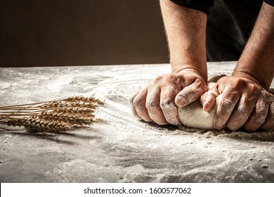 Hands of baker kneading dough isolated on black background. prepares ecologically natural pastries.