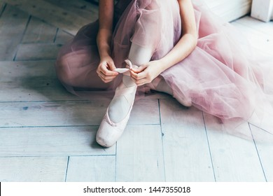 Hands of ballerina in pink tutu skirt puts on pointe shoes on leg in white light hall. Young classical ballet dancer girl in dance class