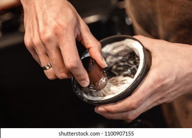 hands of barber with brush for shaving beard and bowl. barber shop