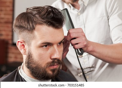 The hands of barber making haircut to young man in barbershop