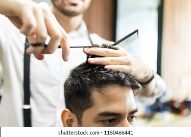 Hands of barber using scissors to cut customer's hair in salon