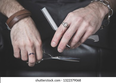 the hands of a barber who hold two of his main tools