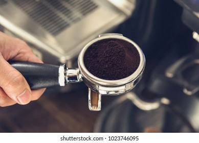 Hands of barista holding portafilter filled with ground coffee preparing to brew with machine