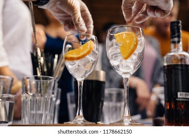 hands of the barman and two glasses with ice and orange slices