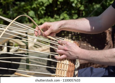 hands of a basket maker weave a wicker basket