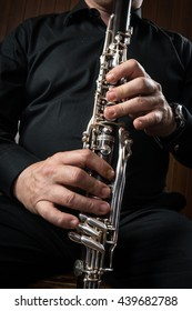 hands of a basset horn player in black