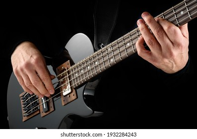 mains de bassiste jouant sur scène une mini-basse électrique noire