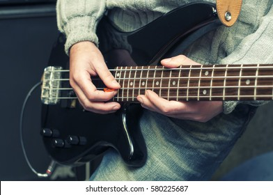 hands of bassist playing a micro bass guitar,blue image