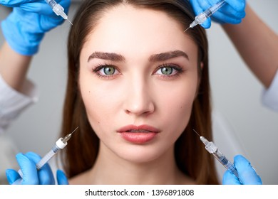Hands of beauticians holding syringes around flawless woman face ready for injection in cosmetology clinic. Female model surrounded with filler syringes. Modern beauty standard concept. Mesotherapy.