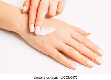 Woman's hands with beautiful manicure applying moisturizing skincare cream.