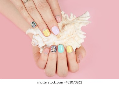 Hands with beautiful manicured nails and sea shell