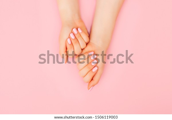 Hands of a beautiful woman on a pink background. Delicate hands with natural manicure, clean skin. Light pink nails.