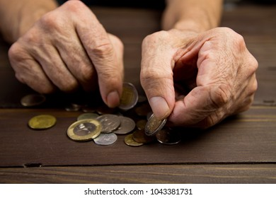 Hands of beggar with few coins. The concept of poverty . An elderly person on pension holds coins on wooden table background