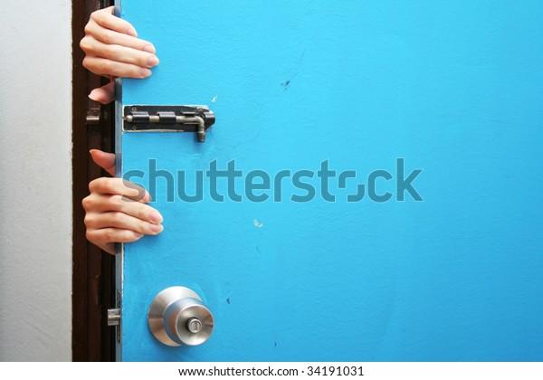 Hands behind a blue door