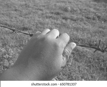 hands and black barbed wire. Black and white tone