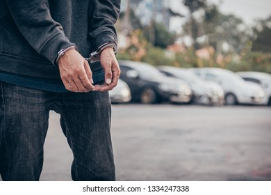 Hands in black gloves with police handcuffs on car background