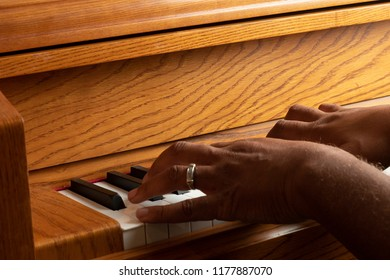 Hands of a black man playing a piano
