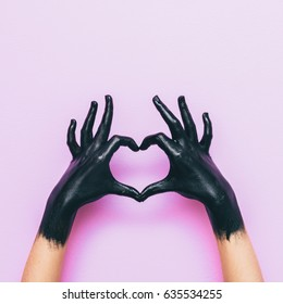 hands in black paint send heart. love and minimal fashion concept.