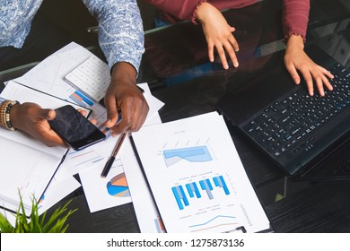 Hands of black people holding mobile phone on background of financial documents in business space close-up