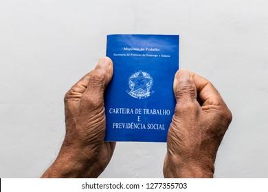 hands of black senior man holding work book, Brazilian social security document