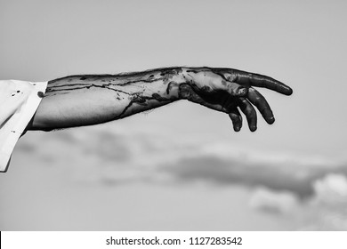 Hands in the blood. zombie male hand of man war soldier with bloody wounds and red blood on skin on blue sky background
