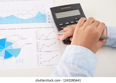 Hands of bookkeeper calculating income of subdivisions
