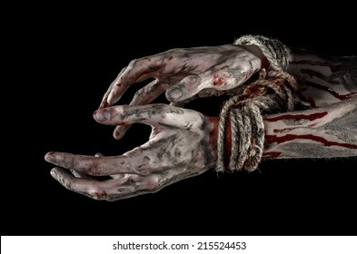 Hands bound,bloody hands, mud, rope, on a black background, isolated, kidnapping, zombie, demon