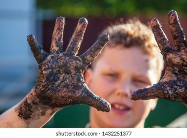 Hands of a boy in black mud on nature .