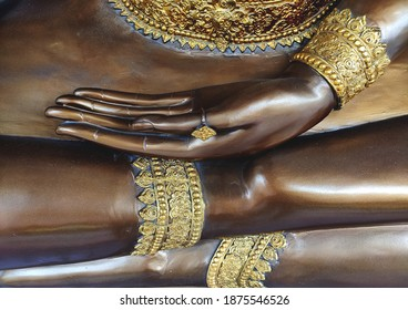 Hands of Brass Buddha statue with gold accessories  in the buddhist temple, in public area.