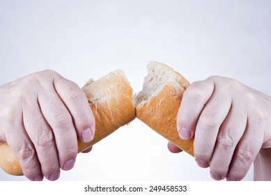 Hands breaking and dividing loaf of bread