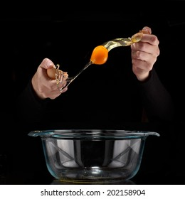 Hands breaking an egg. Egg Yolk dripping, falling, on black background.