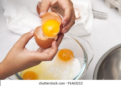 Hands Breaking eggs in a bowl for cooking a cake