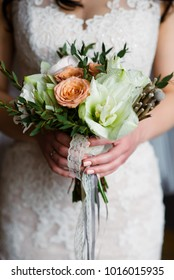 Hands of the bride and the bridal bouquet.