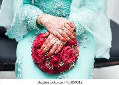 Hands of Bride With Flower bouquet. Malay Wedding Dress And Bouquet Of Flowers. Selective Focus And Shallow DOF.