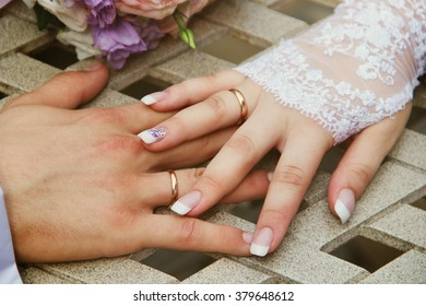 Hands of the bride and groom each other