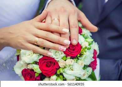 hands of bride and groom on a beautiful wedding bouquet