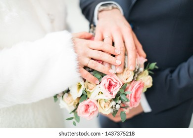 Hands of the bride and groom on a bouquet