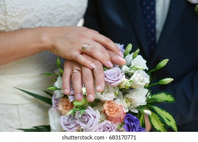 Hands of the bride and groom on a bridal bouquet