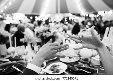 Hands of the bride and groom with rings at the banquet.
