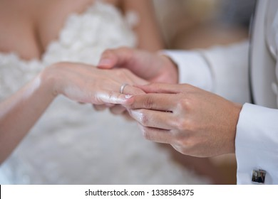 Hands of bride and groom in solemn process of exchanging rings, symbolizing the creation of new happy family. Groom putting a ring on bride's finger during wedding ceremony.