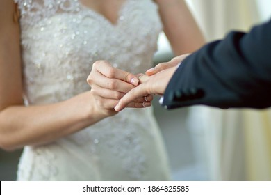 Hands of bride and groom in solemn process of exchanging rings, symbolizing the creation of a new happy family. Bride putting a ring on groom's finger during the wedding ceremony. Soft focus image.