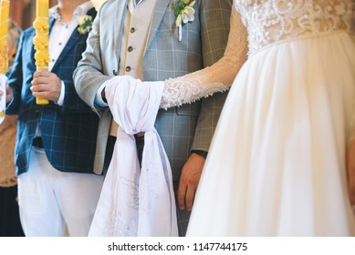 hands of bride and groom tied by towel at church