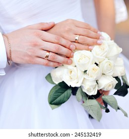 hands of the bride and groom with wedding rings on bouquet.