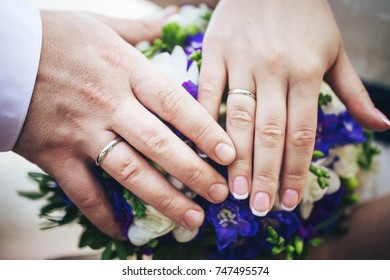 Hands of the Bride and Groom with Wedding Rings on a Wedding Bouquet
