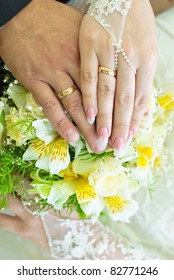 Hands of bride and groom with wedding rings over the bridal bouquet