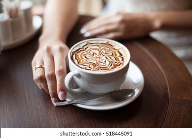 Hands of bride with latte art coffee cup. Selective focus. Marriage concept